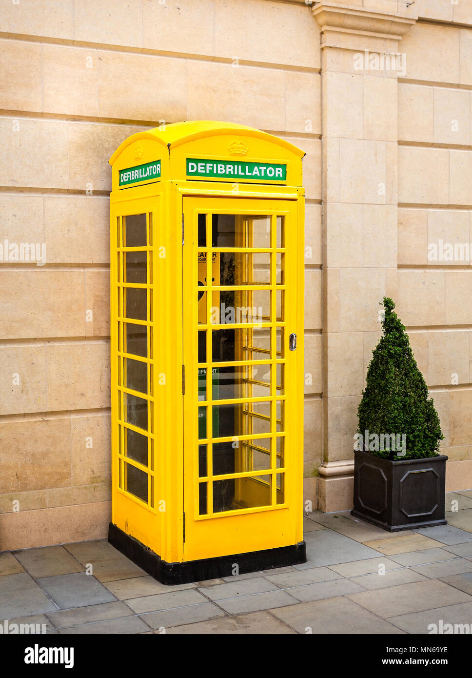 Defibrillator in yellow telephone kiosk in Southgate Shopping Centre, Bath, Somerset, UK taken on 13 May 2018 - Stock Image