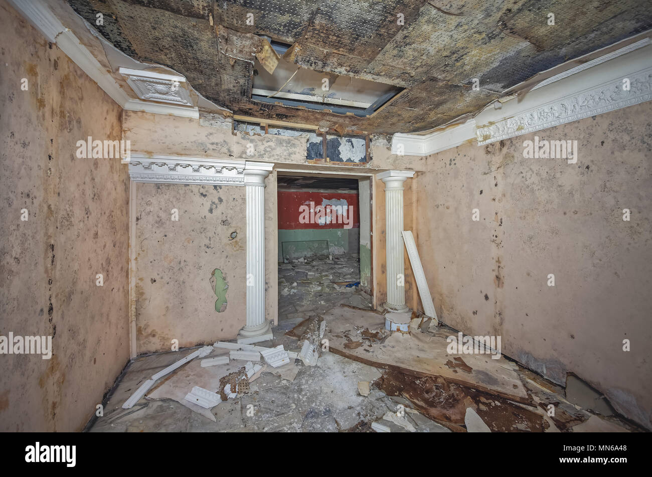 Room in an old abandoned Soviet shelter with decorative antique columns and garbage on the floor. Dampened suspended ceiling with mold. Stock Photo