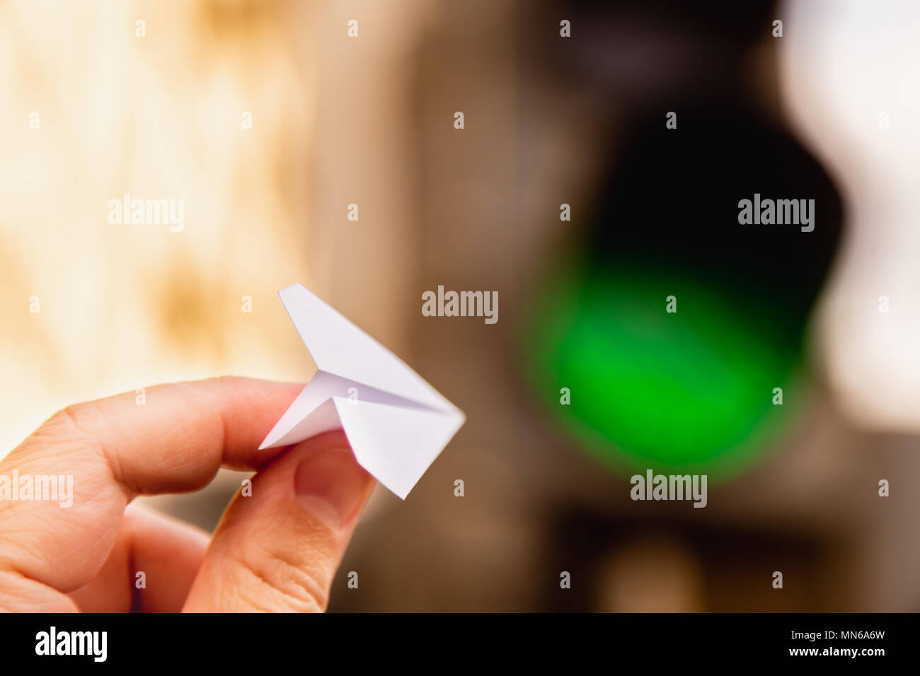 One Small Paper Airplane In Hand Against A Traffic Light Background Diagrams With Glowing Green Signal Permission To Fly Takeoff Is Approved And Allowed H