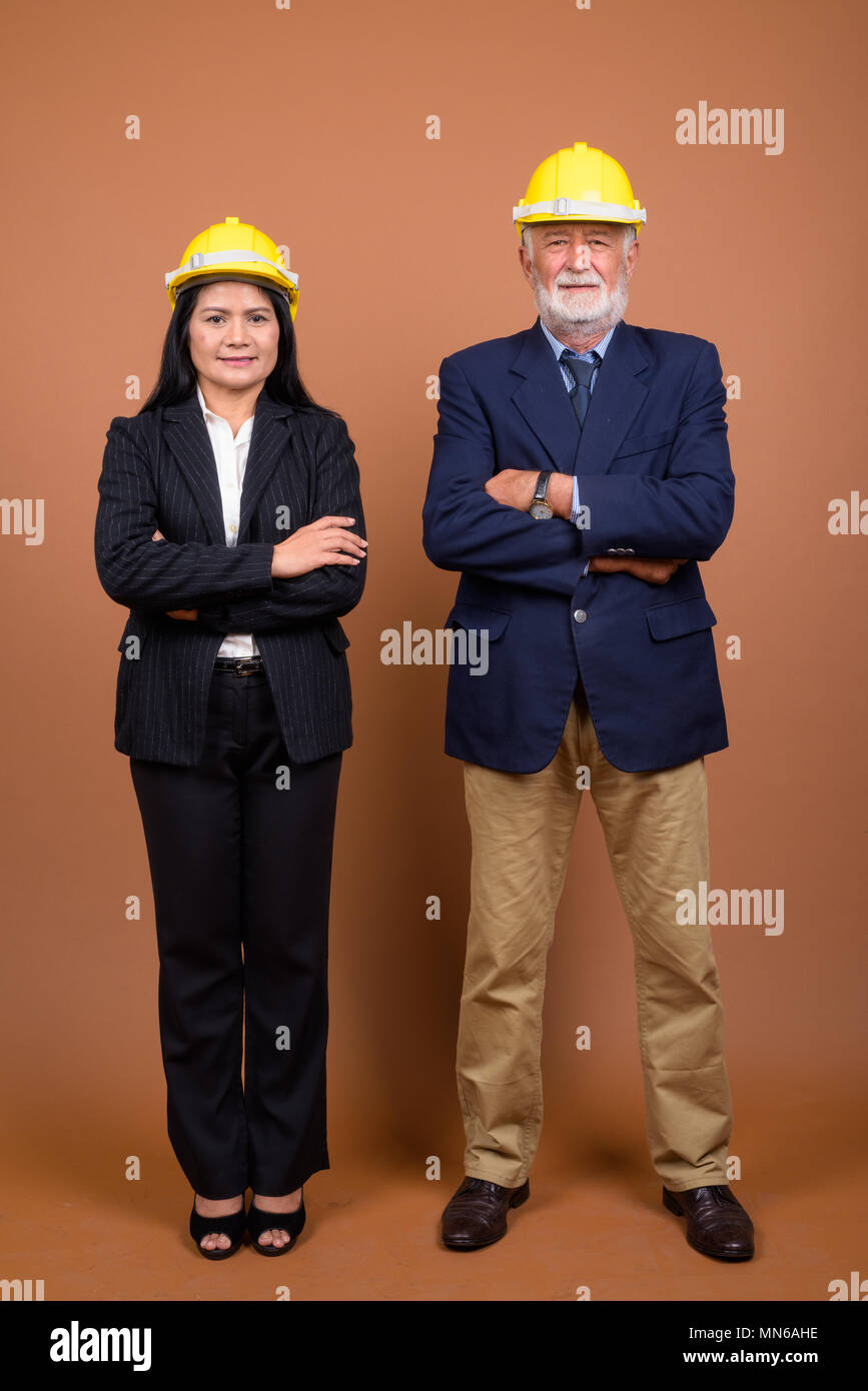Mature multi-ethnic business couple against brown background - Stock Image