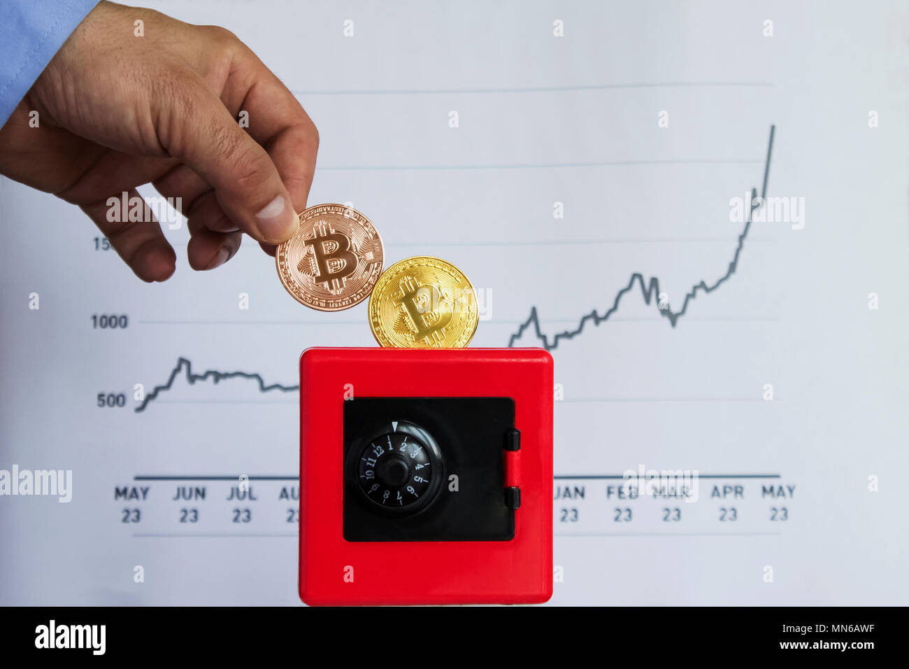 A business man who saves his earned bitcoin money, throws coin in a red safe, with a bitcoin diagram in the background|gold|blue|sleeve - Stock Image