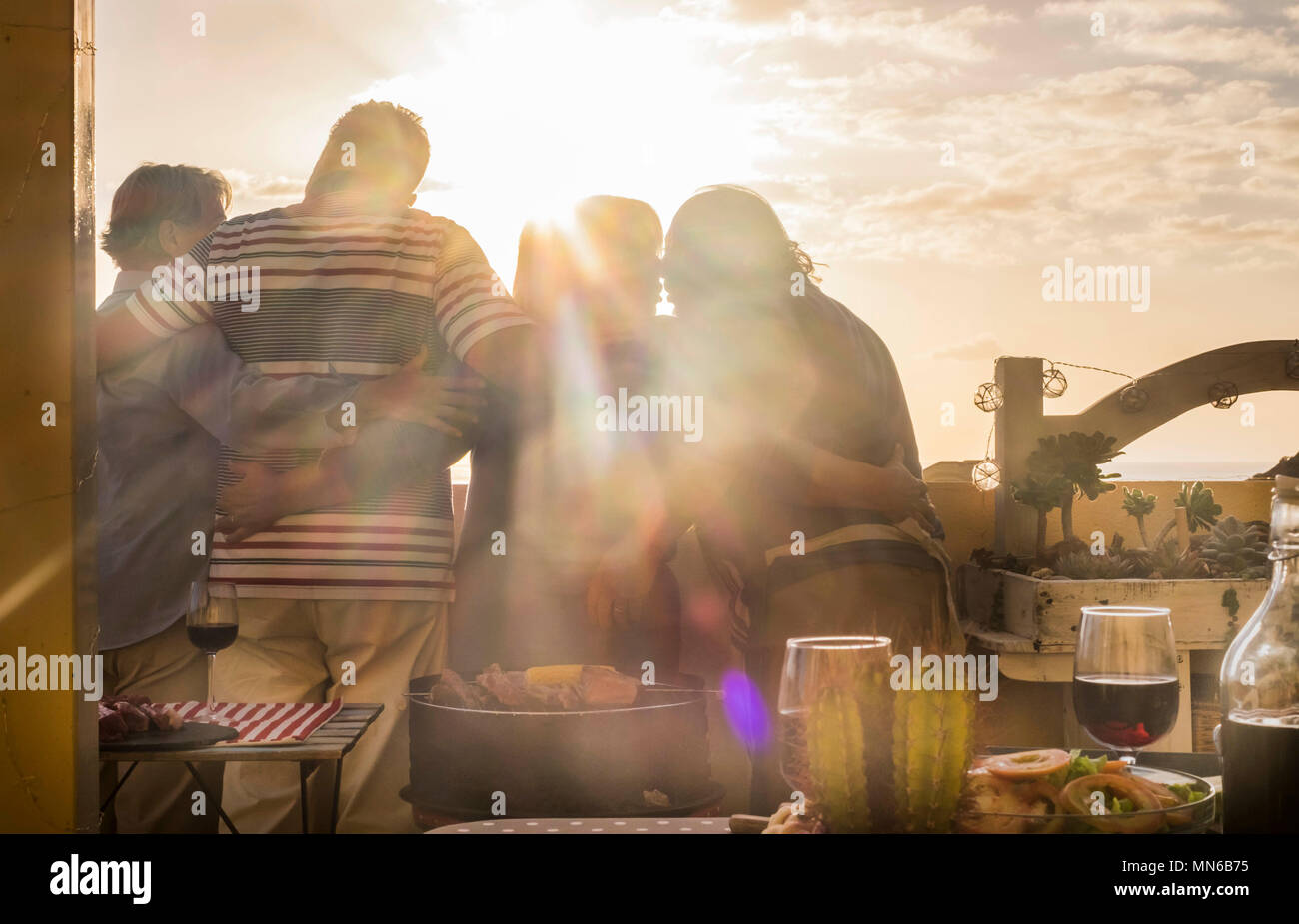 Group of four caucasian friends mature over 70 retired celebrate love and friendship in front of a golden sunset from a terrace rooftop. dinner on the - Stock Image