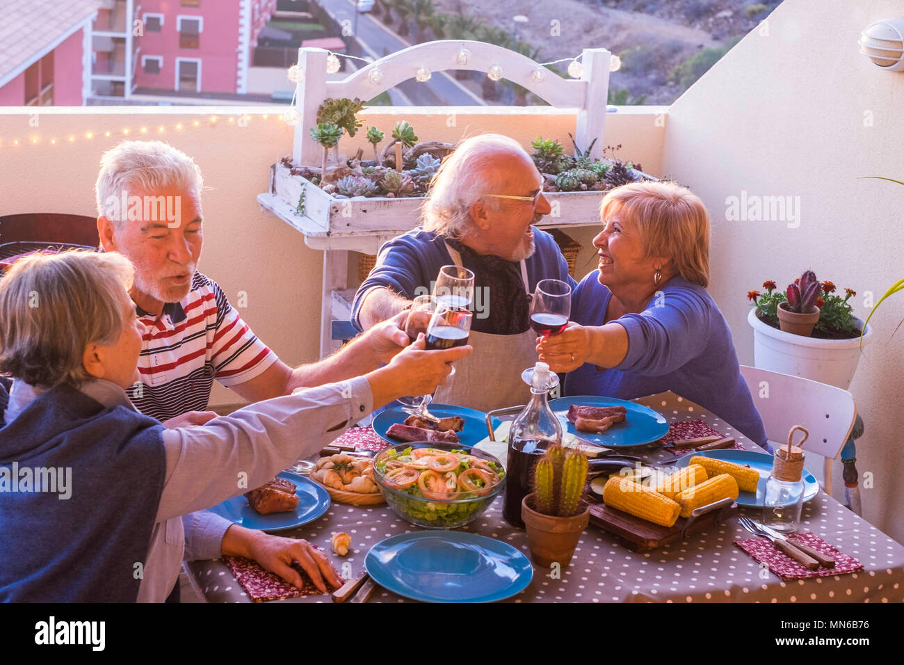 Celebration time at dinner on the rooftop for group of cacuasian senior adult during event. party time with wine and food pon the table. together leis - Stock Image