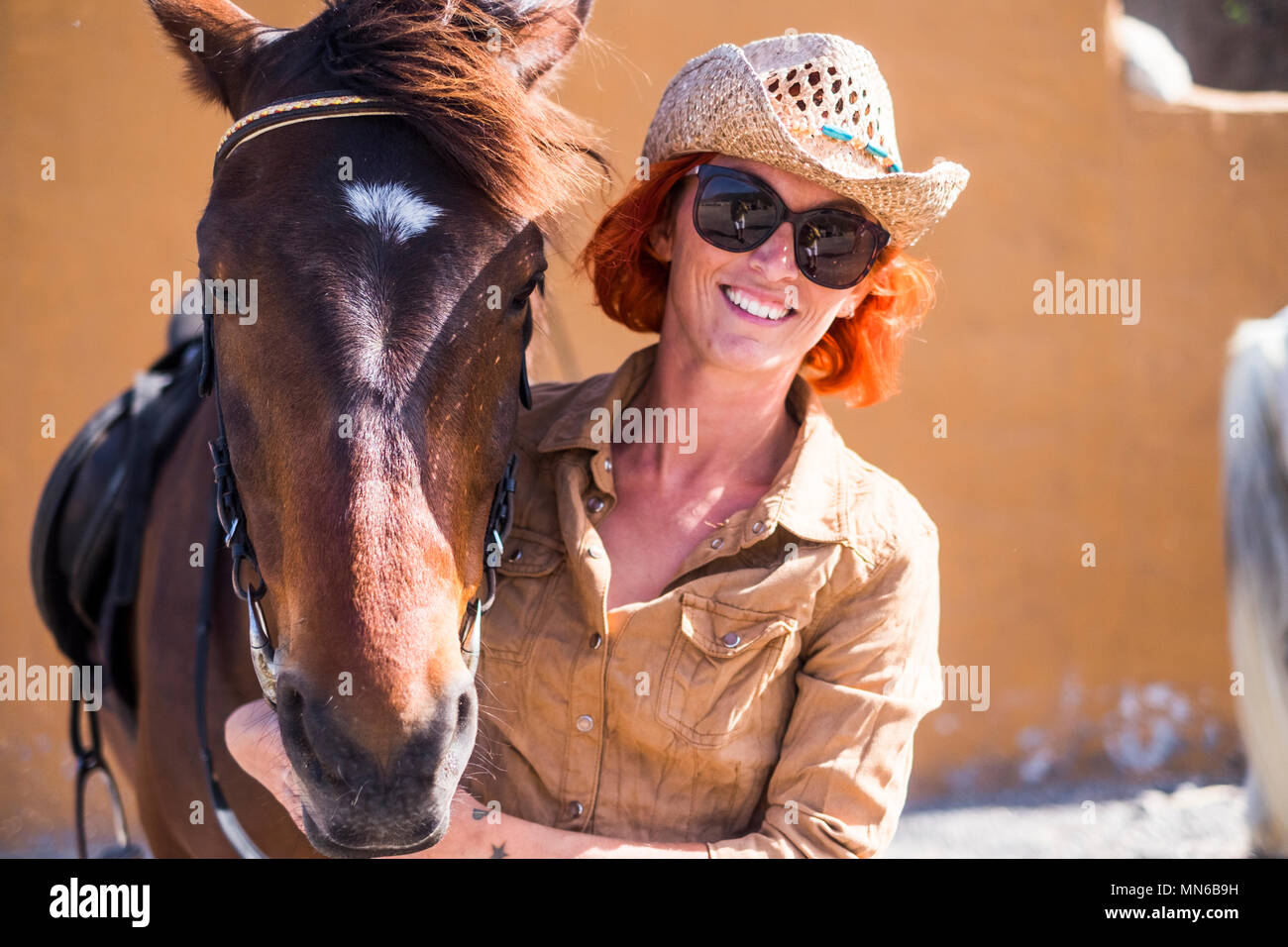 smiled beautiful girl red hair and cowboy hat with her best friend horse in friendship ready to live another adventure outdoor in leisure activity und - Stock Image