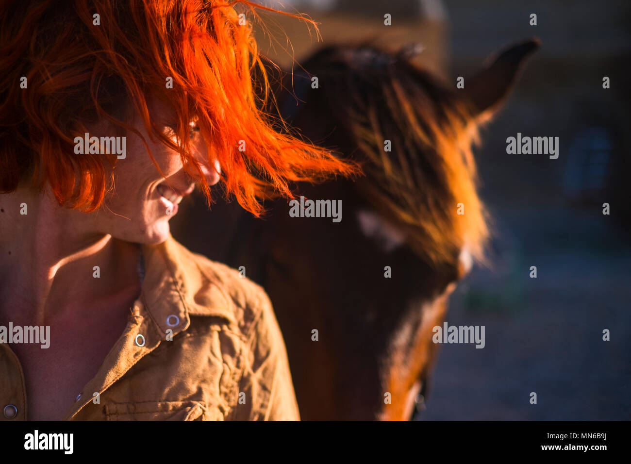 red hair beautiful young woman lifestyle with best friend horse in countryside. portrait of paople and animals for pet life concept outdoor under the  - Stock Image