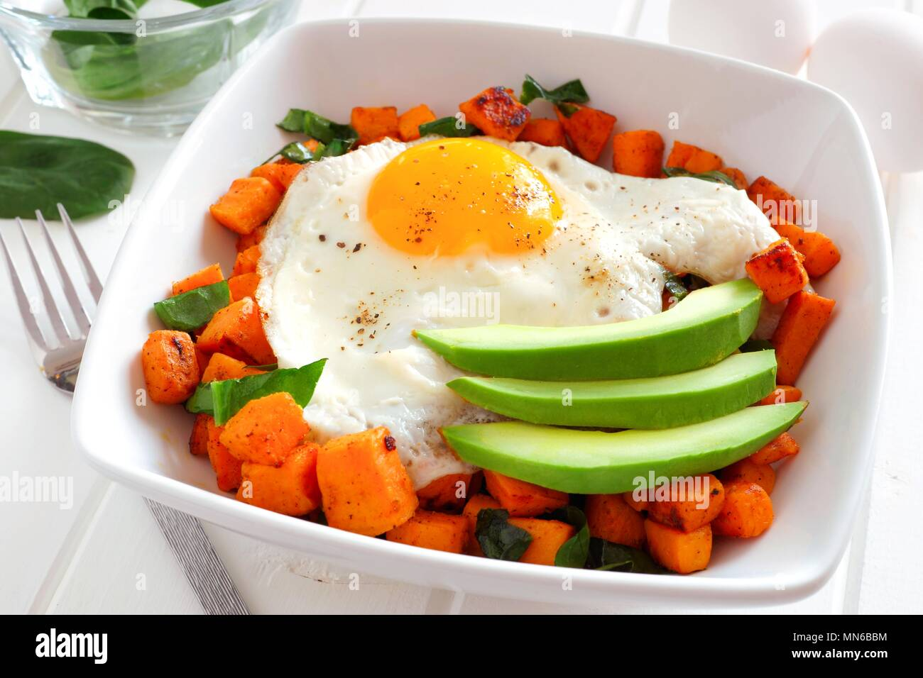 Breakfast nutrient bowl with sweet potato, egg, avocado and spinach, close up table scene - Stock Image
