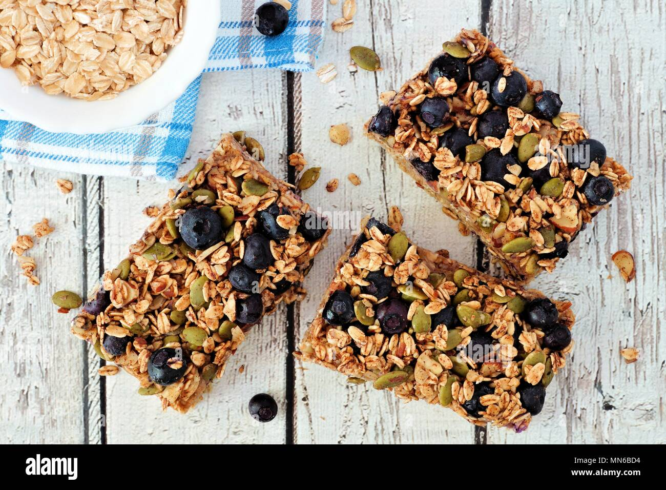 Superfood breakfast bars with oats and blueberries, overhead on white wood background - Stock Image