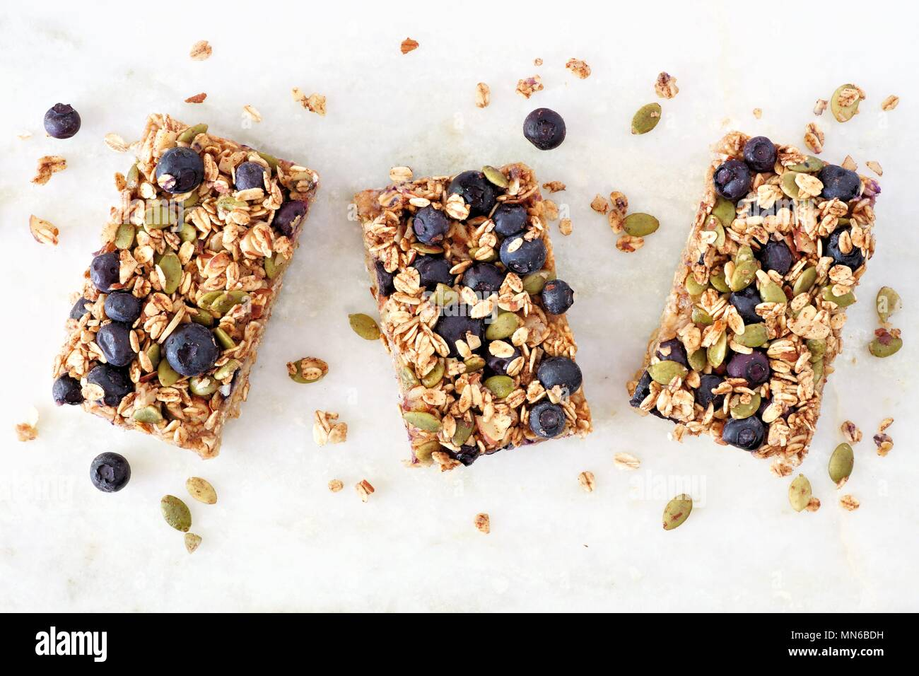 Superfood breakfast bars with oats and blueberries, above view on white marble background - Stock Image