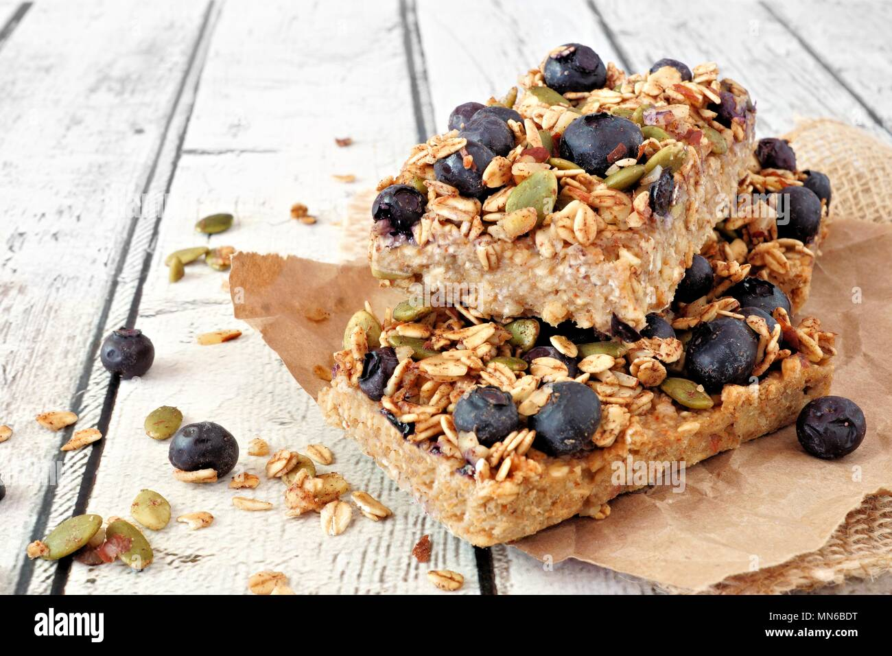 Two stacked superfood breakfast bars with oats and blueberries, side view on rustic white wood - Stock Image