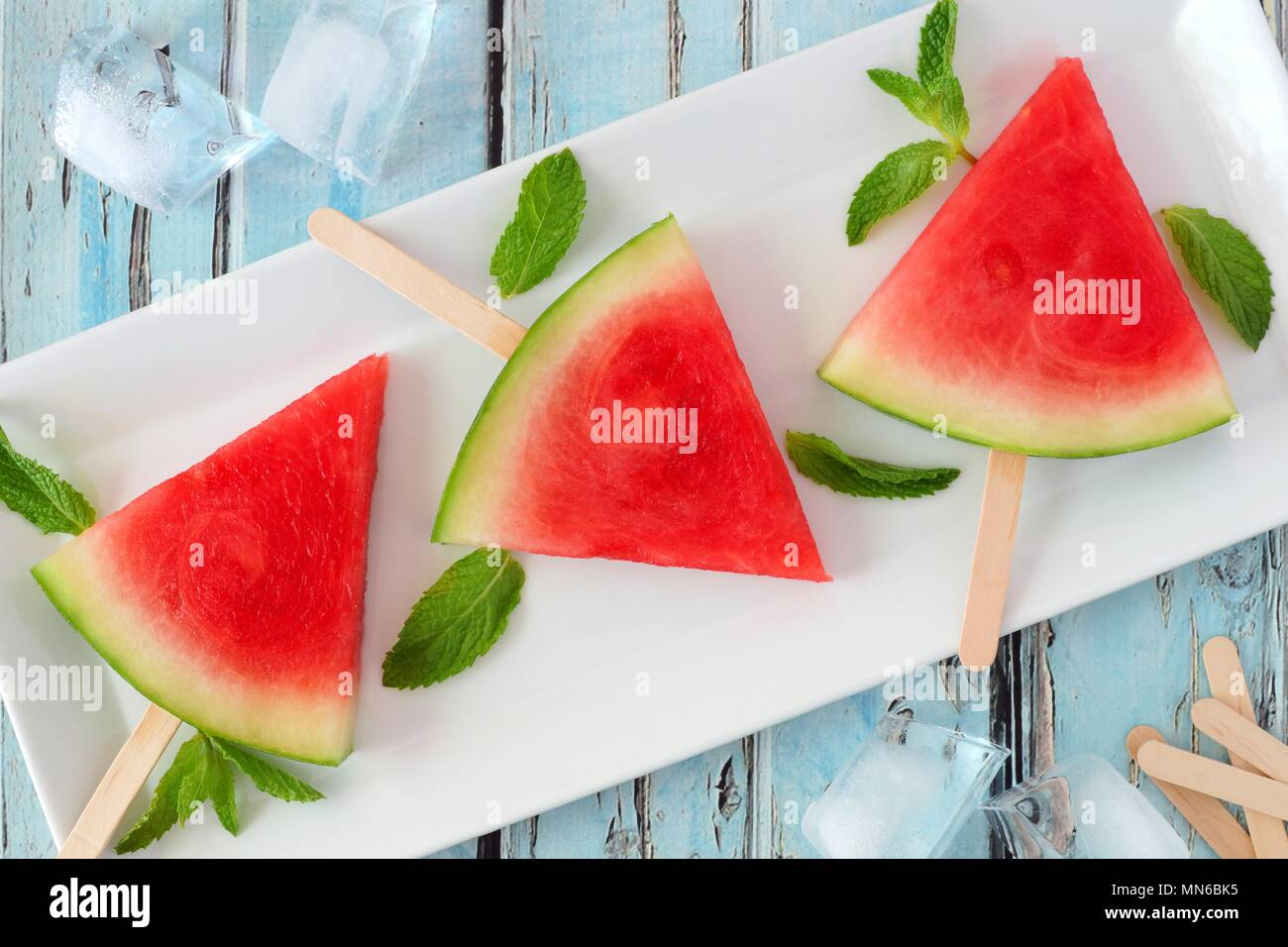 Group of watermelon slice popsicles on a white plate with rustic blue wood background - Stock Image