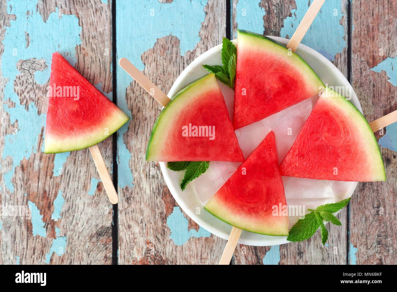 Watermelon slice popsicles on plate with a rustic blue wood background - Stock Image
