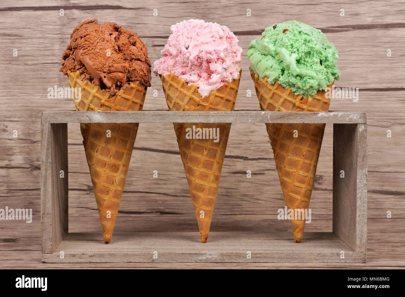 Chocolate, cherry and pistachio ice cream in waffle cones in rustic holder over a wood background - Stock Image