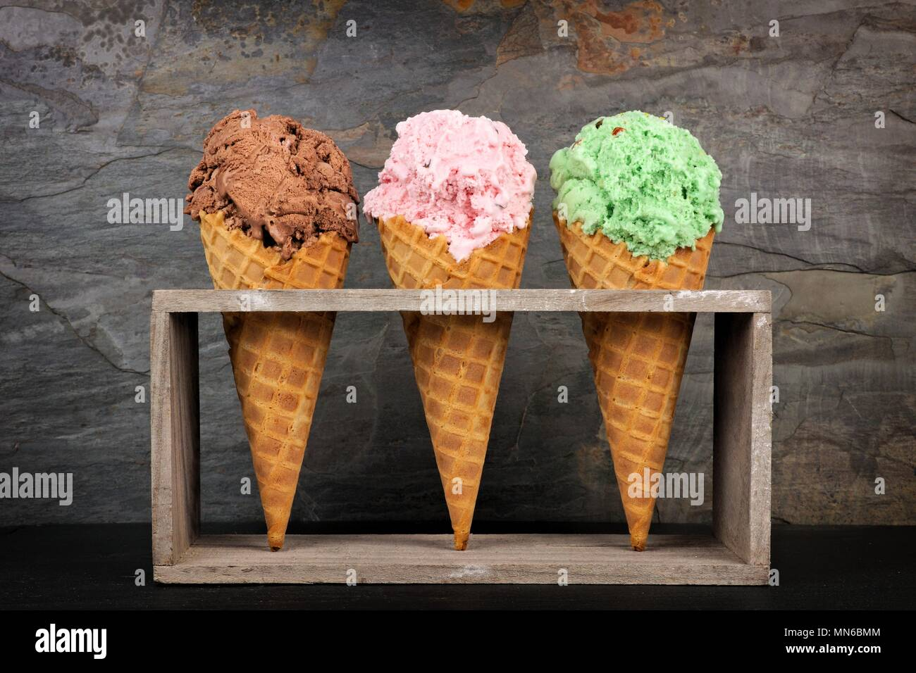 Chocolate, cherry and pistachio ice cream in waffle cones in rustic wood holder over a slate background - Stock Image