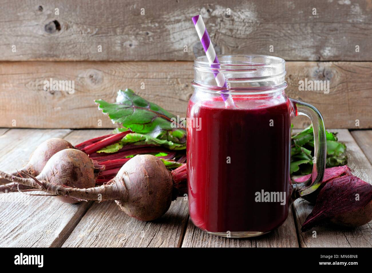Fresh beet juice in a mason jar glass with beets over a rustic wood background - Stock Image
