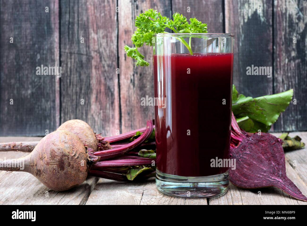 Beet juice in a glass against a rustic wooden background - Stock Image