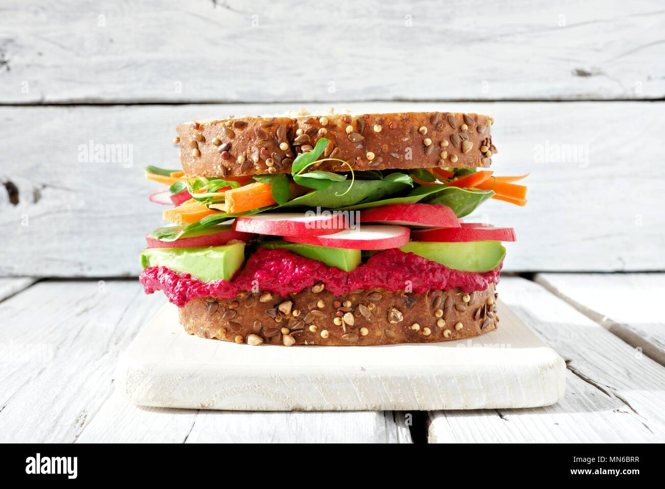 Superfood sandwich with beet hummus, avocado, vegetables and greens, on whole grain bread against a white wood background - Stock Image