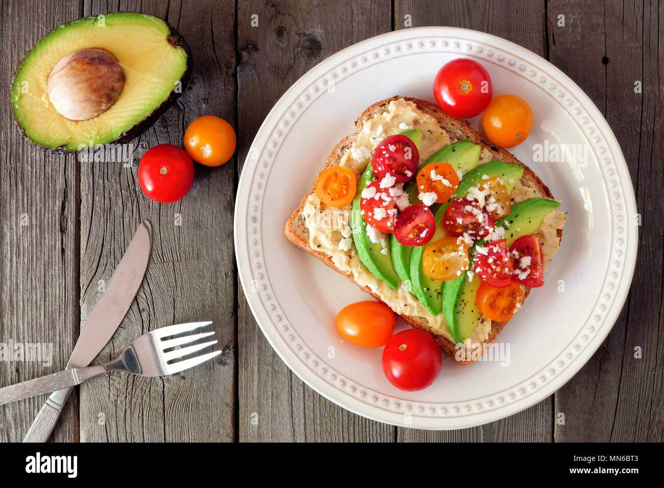 Avocado toast with hummus and tomatoes on plate, above scene on old wood background Stock Photo