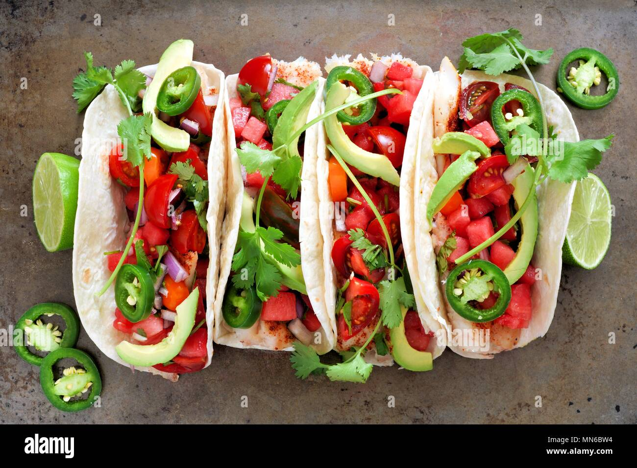 Spicy fish tacos with watermelon salsa and avocados, above view on rustic metallic background - Stock Image