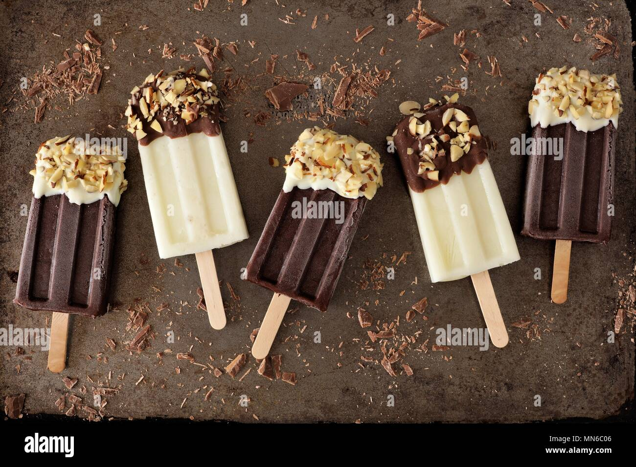Chocolate and almond dipped white and dark popsicles, on rustic metallic background - Stock Image