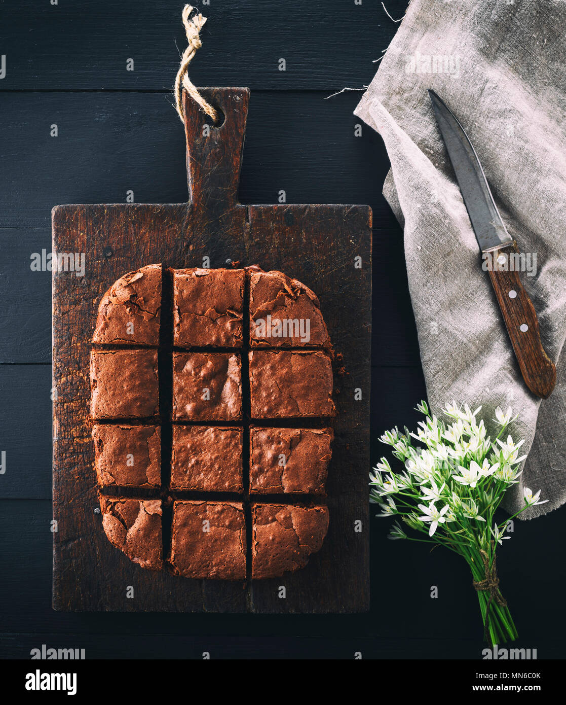 baked rectangular chocolate brownie pie is cut into squares, a wooden black table - Stock Image
