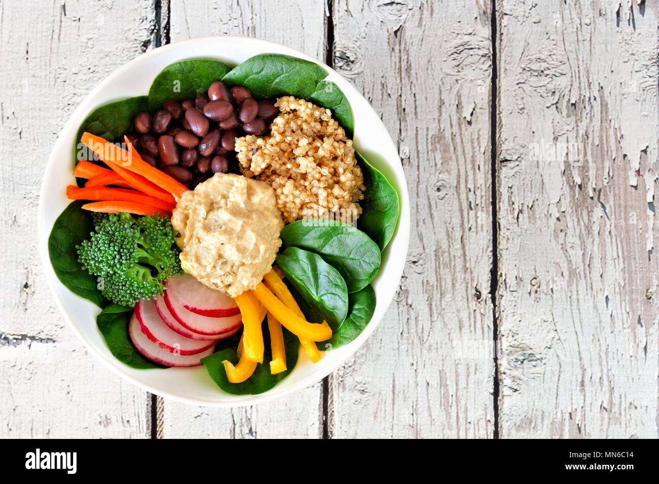Nourishment lunch bowl with quinoa, hummus and mixed vegetables, above view on rustic white wood - Stock Image