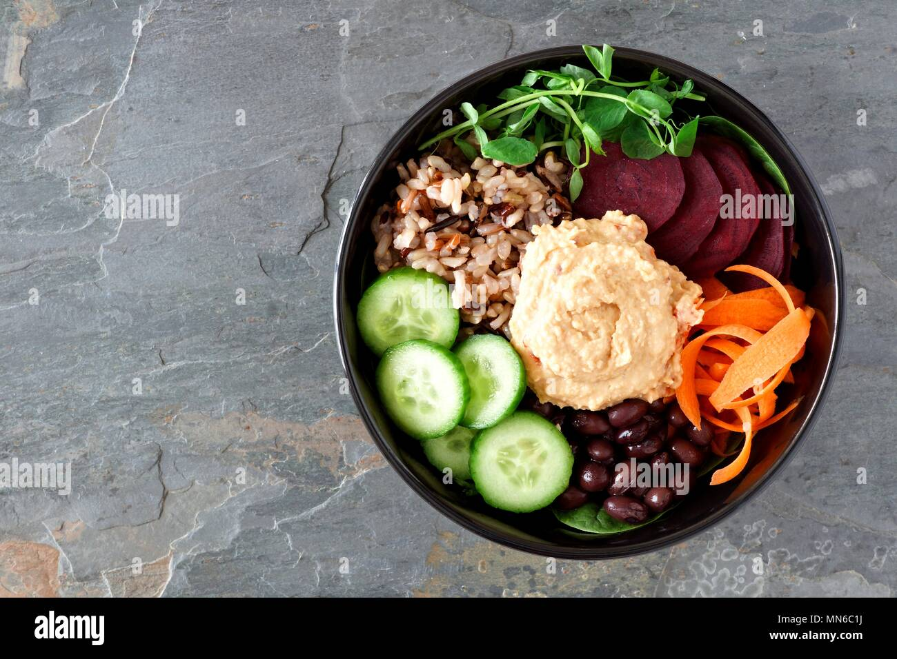 Healthy vegetarian salad bowl with hummus, beans, wild rice, beets, carrots, cucumbers and pea shoots. Above view on slate background. - Stock Image