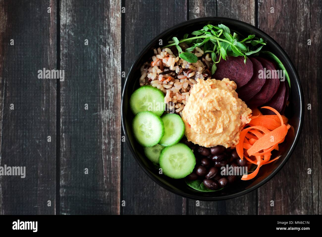 Healthy vegetarian nourishment bowl with hummus, beans, wild rice, beets, carrots, cucumbers and pea shoots. Above view on dark wood. - Stock Image