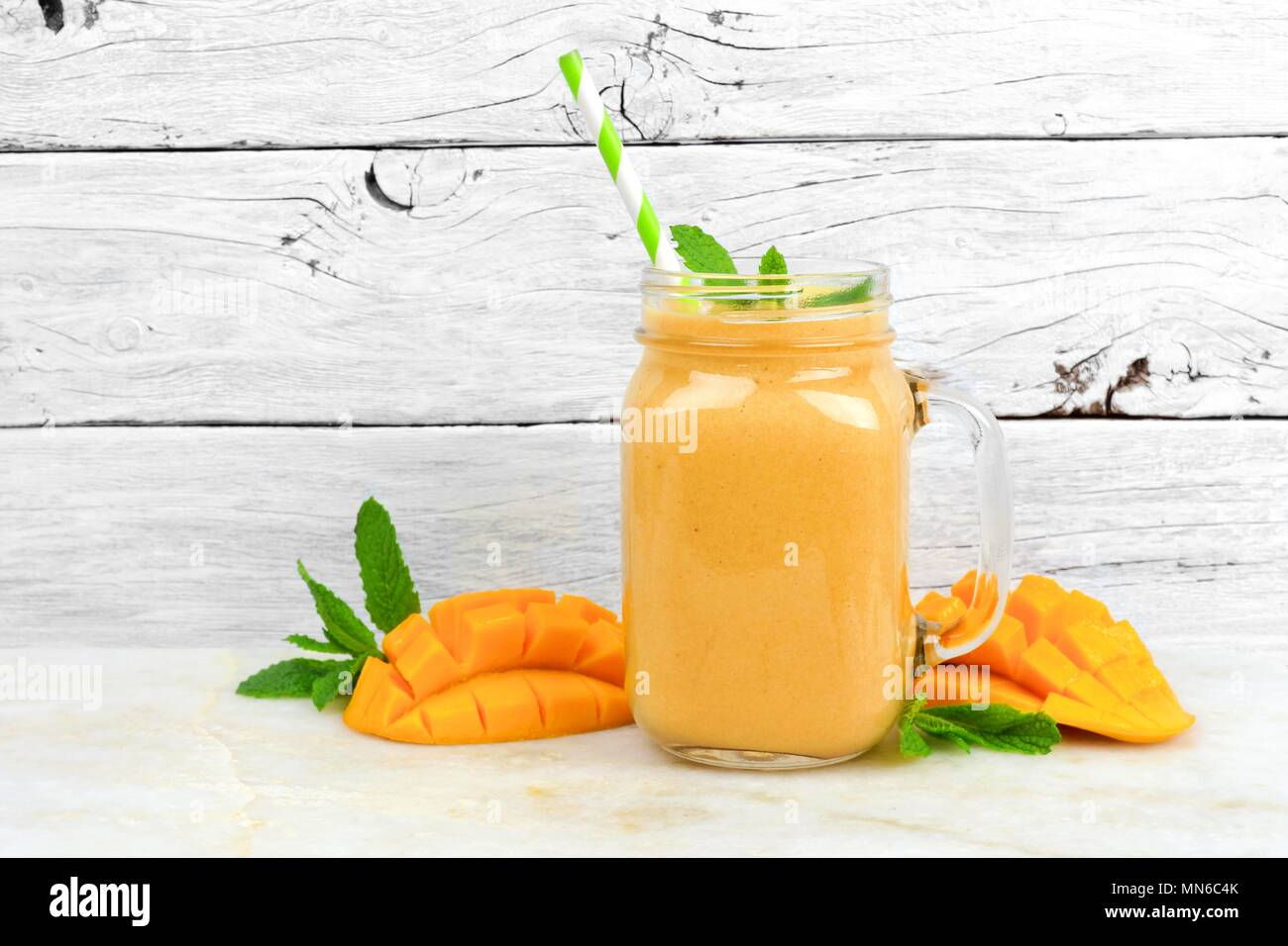 Tropical mango coconut smoothie in a mason jar glass, on a rustic white wood background Stock Photo