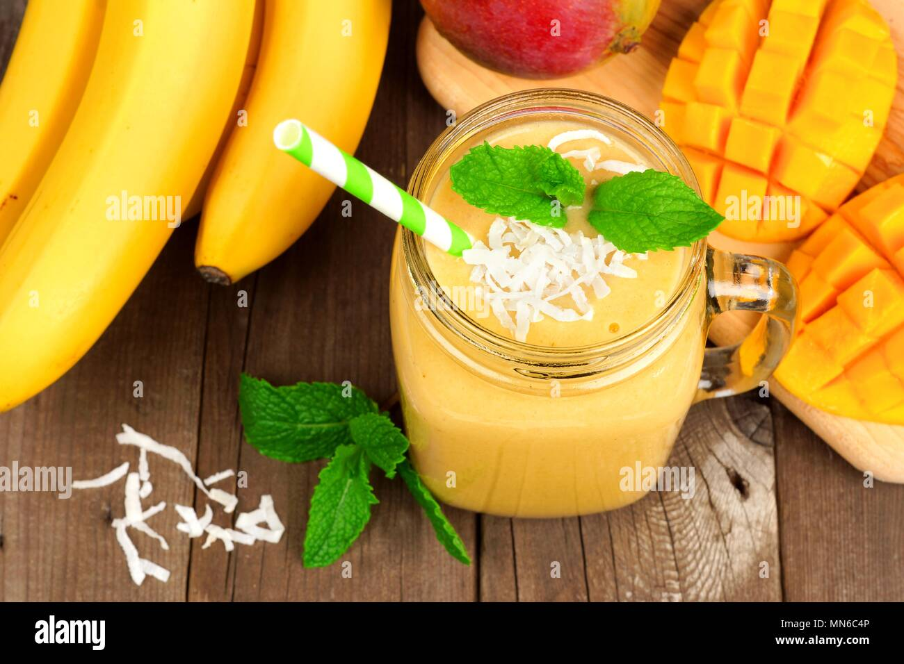 Mango, banana, coconut smoothie in a mason jar glass, overhead view on a rustic wood background - Stock Image