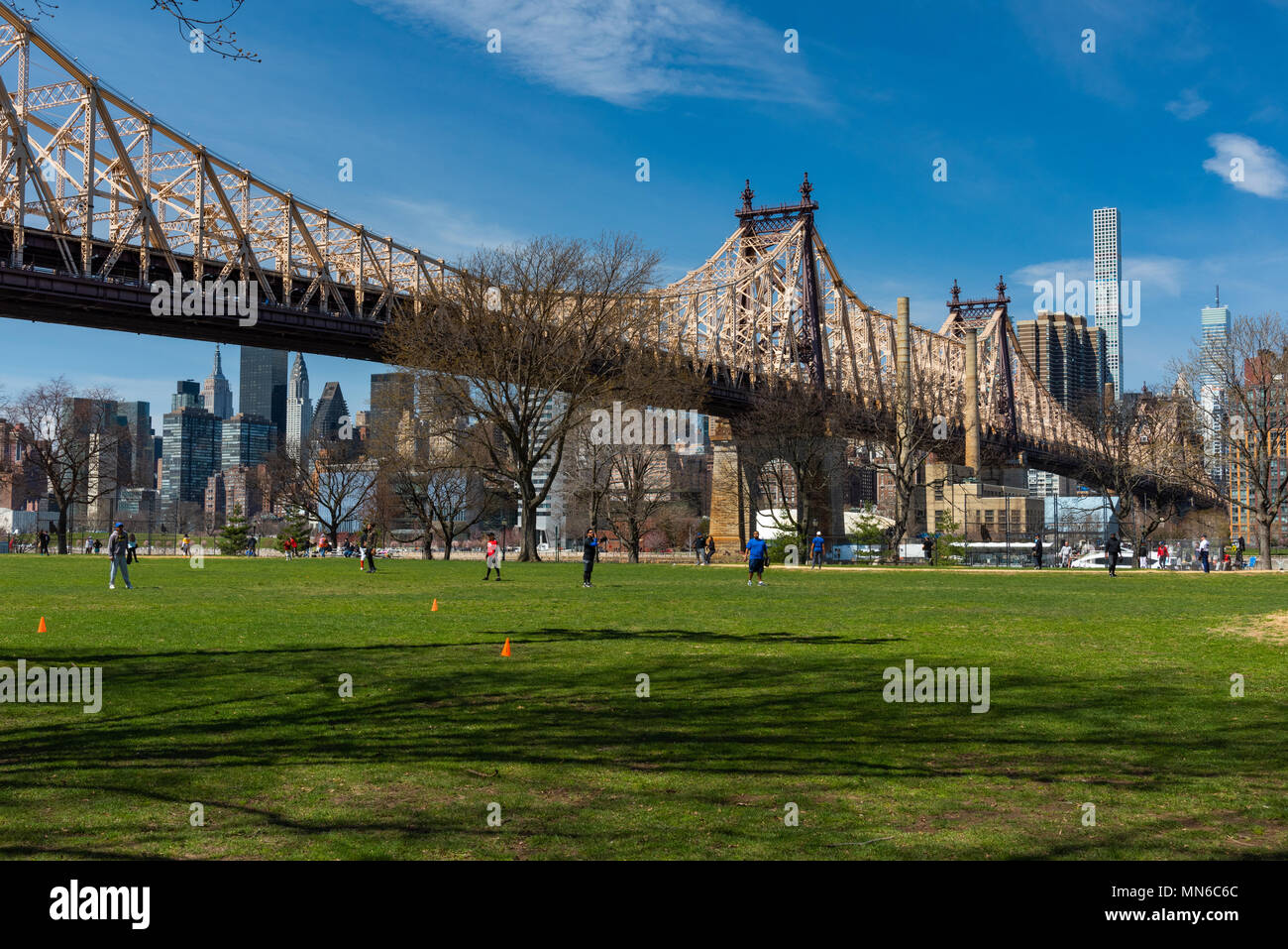 New York, USA -  April 21, 2018:  People playing baseball at Queensbridge Park in a sunny day. Ed Koch Queensboro Bridge in the background Stock Photo