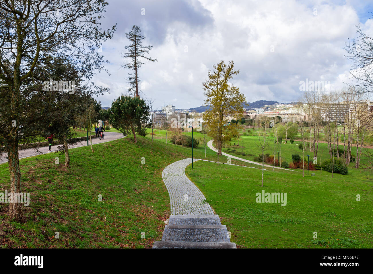 Empty cobblestone path, track, trail or pathway through trees and green grass lawn. Parque da Devesa Urban Park. Vila Nova de Famalicao, Portugal - Stock Image