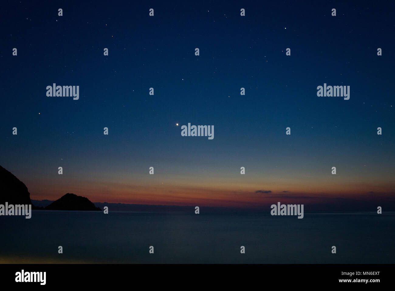 Motion blurred picture of a mediterranean sea at night under a beautiful sky with stars, seen from Petani beach on Cephalonia - Stock Image