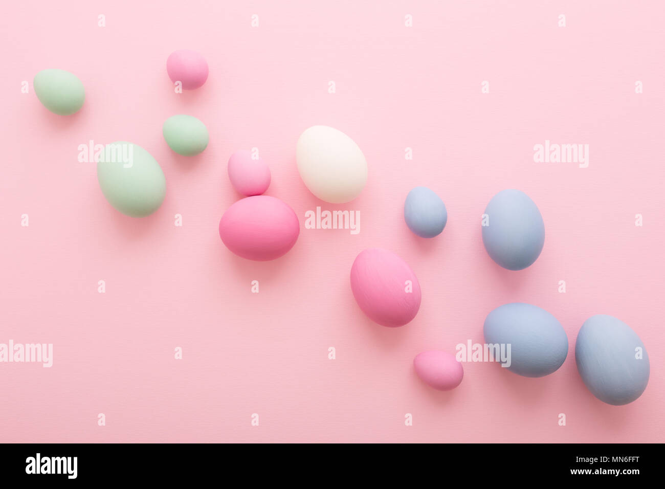 Spreaded colored Easter Eggs on pink  background. Happy Holiday greeting card. Flat lay, minimal style. Pastel colors - Stock Image