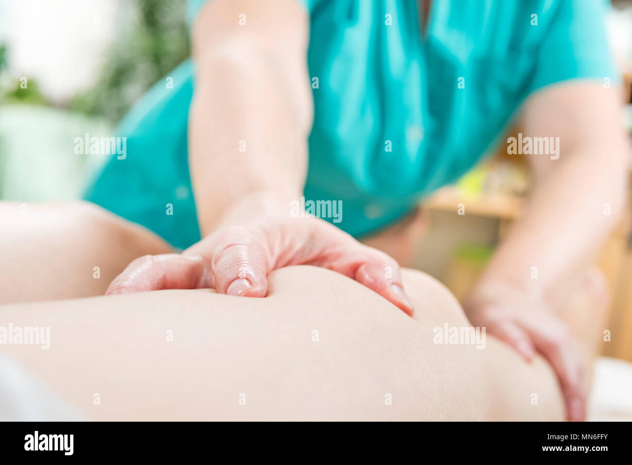 Doctor massages the patient's leg with a force, a blurred background - Stock Image