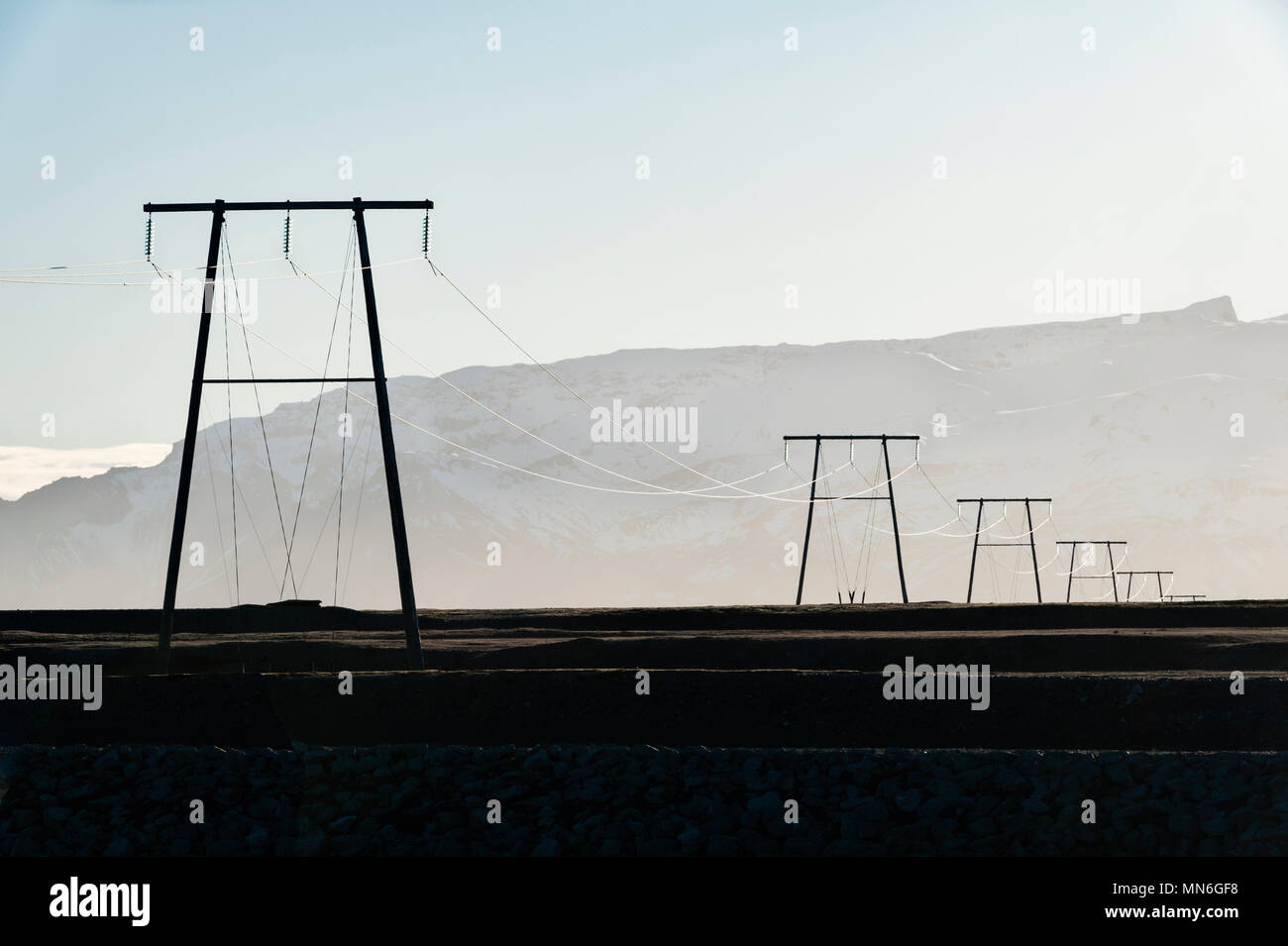 South Iceland. Electricity pylons near the coast. All electrical transmission and distribution is run by the company Landsnet - Stock Image
