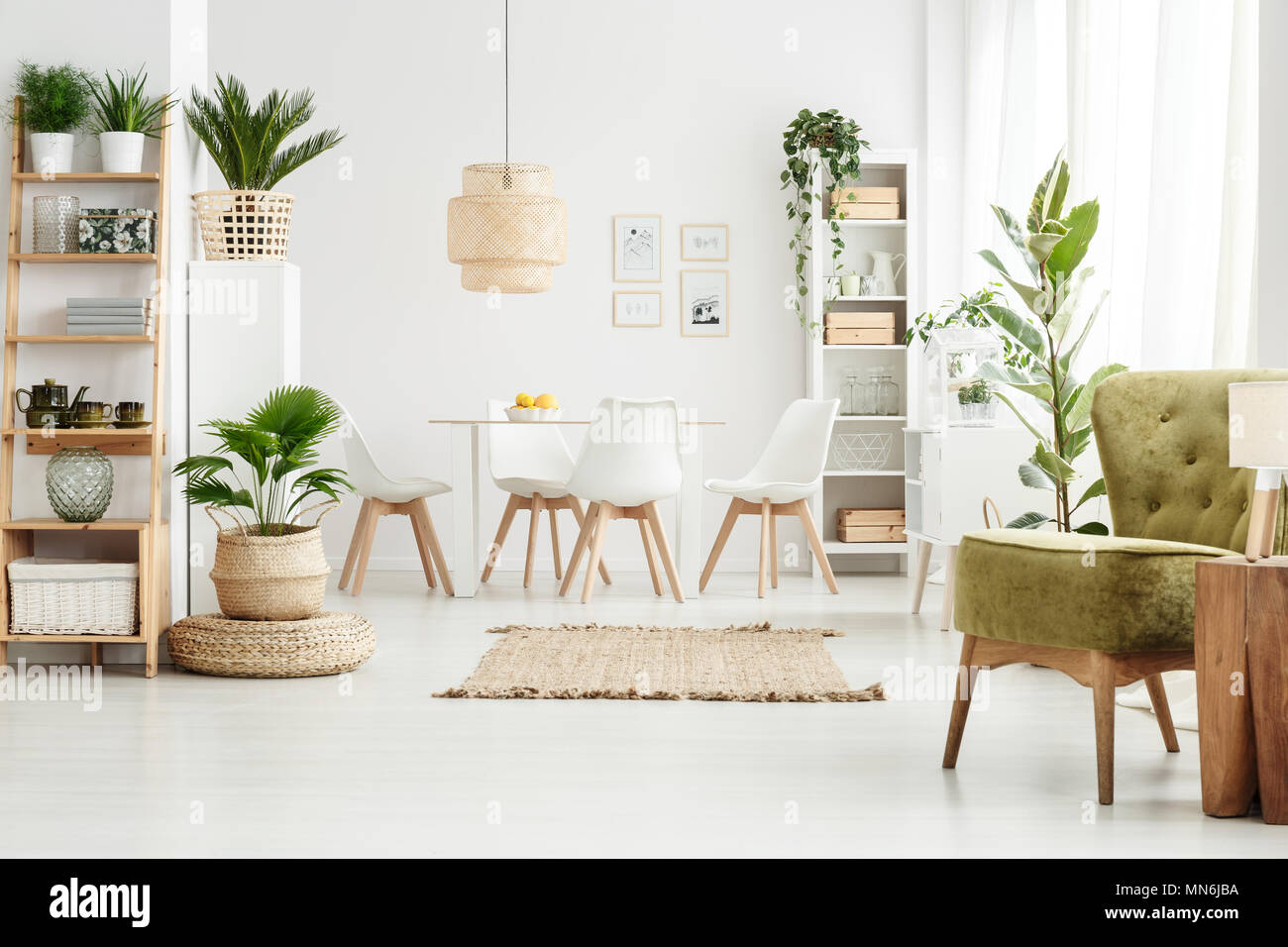 Lamp On Wooden Stool And Green Armchair In Multifunctional Dining Room  Interior With Pouf, Plants And Brown Rug