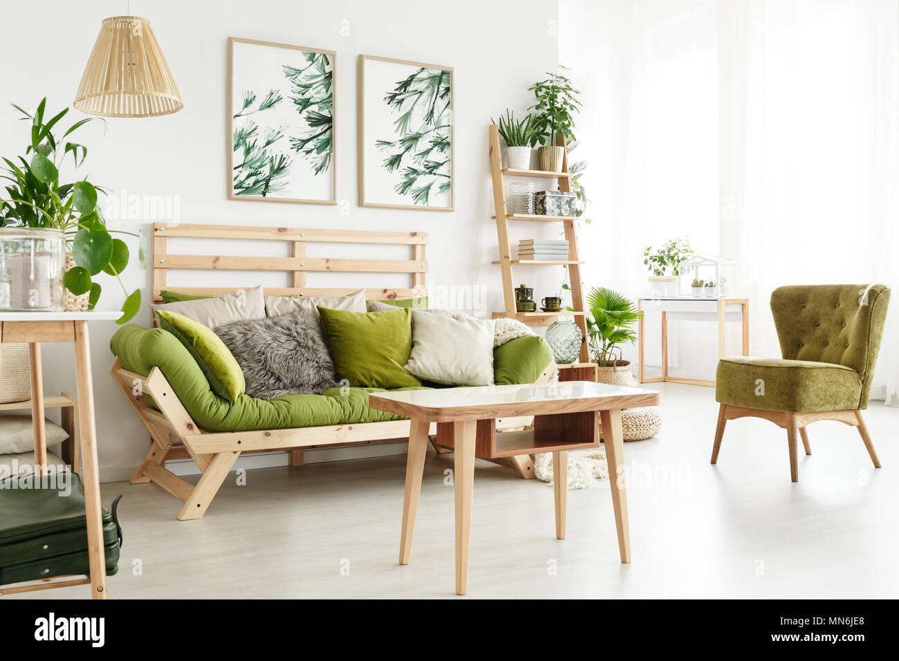 Wooden Table Near Green Armchair And Sofa In Natural Living Room