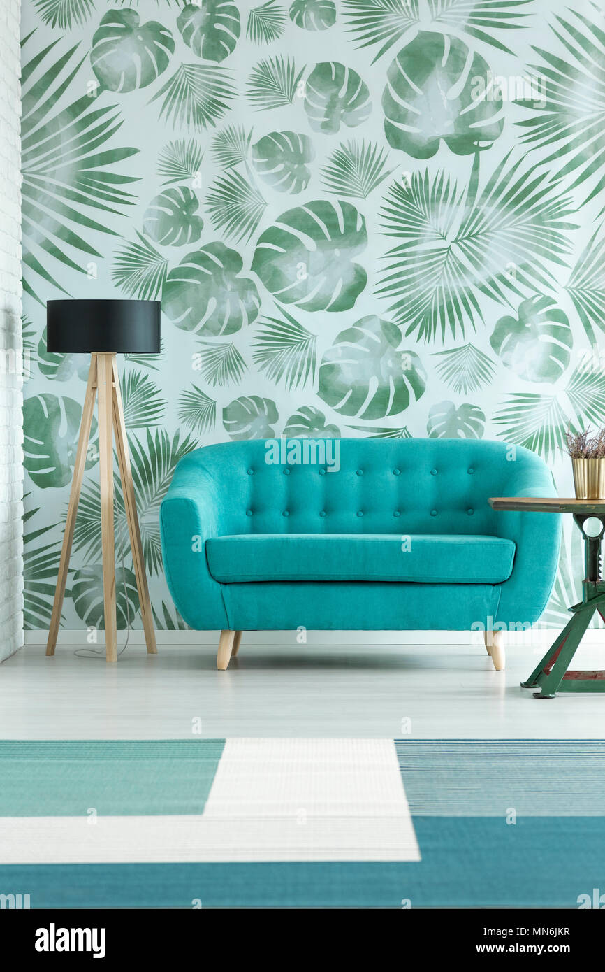 Lamp next to turquoise sofa in floral