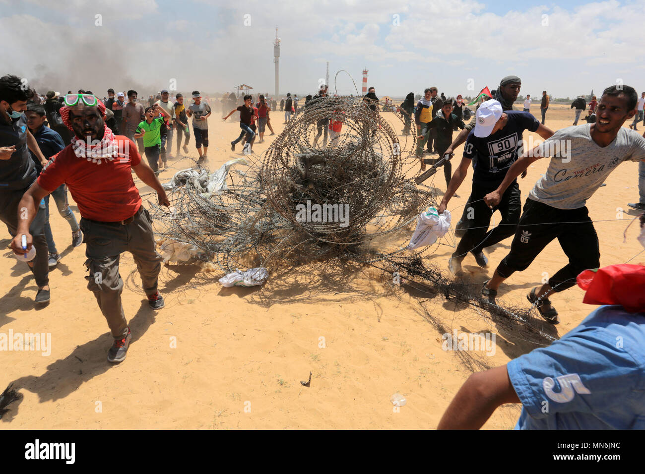 GAZA, PALESTINIAN TERRITORIES - 14 MAY 2018 Palestinian demonstrators gesture towards Israeli forces during clashes along the border with the Gaza Str - Stock Image