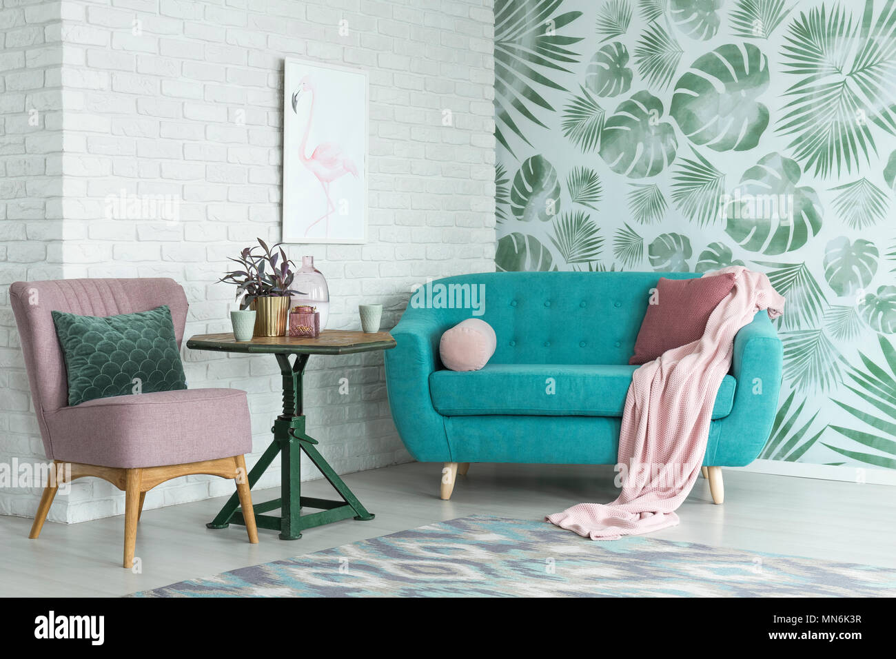 Green table with a plant between pink chair and blue sofa in floral ...