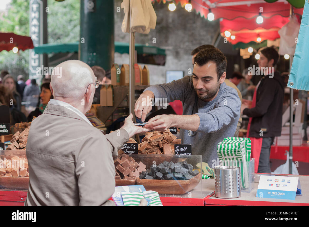 SOUTHWARK, LONDON-SEPTEMBER 7,2017: Man is selling chocolate pieces in stall at Borough Market on September 7, 2017 in London. Borough Market - Stock Image