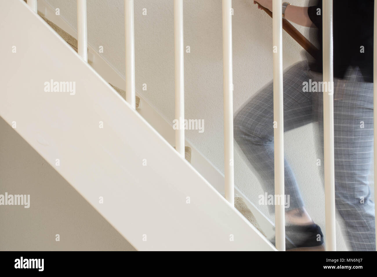 Young adult person walking up the stairs in house Stock Photo