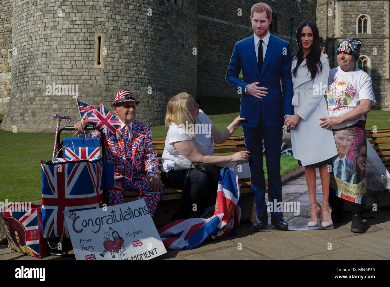 Royalists occupy benches outside Windsor Castle with a life-size standee of Prince Harry and Meghan Markle as the royal town gets ready for the royal wedding between Harry and his American fiance, on 14th May 2018, in London, England. Stock Photo