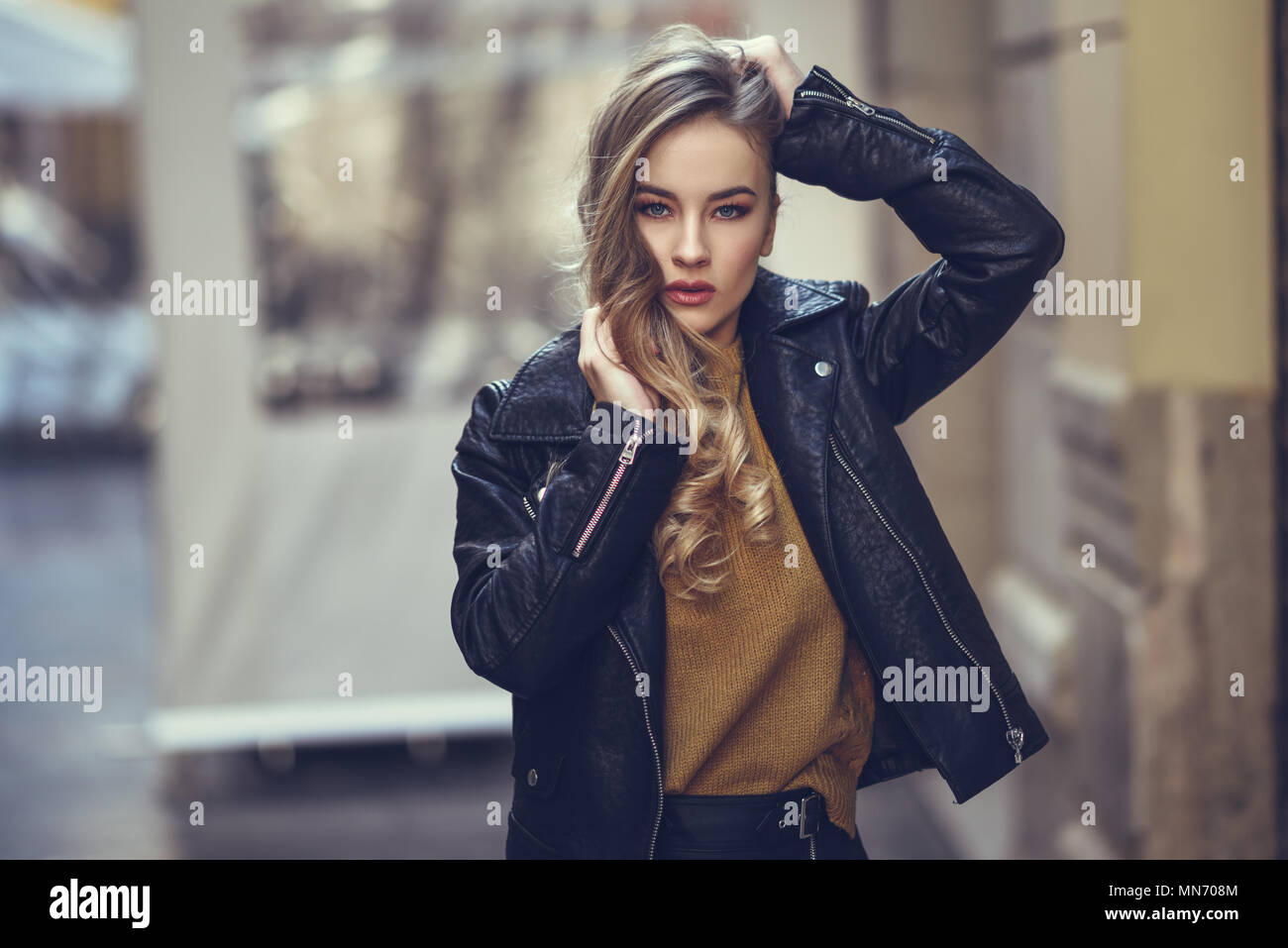 Blonde woman in urban background. Beautiful young girl wearing