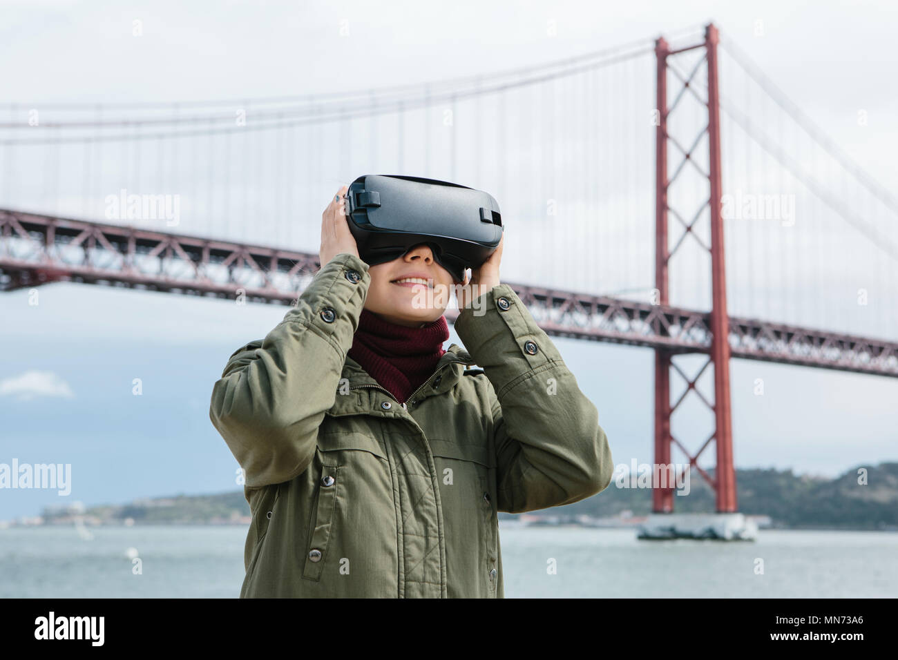 Young beautiful girl wearing virtual reality glasses. 25th of April bridge in Lisbon in the background. The concept of modern technologies and their use in everyday life - Stock Image