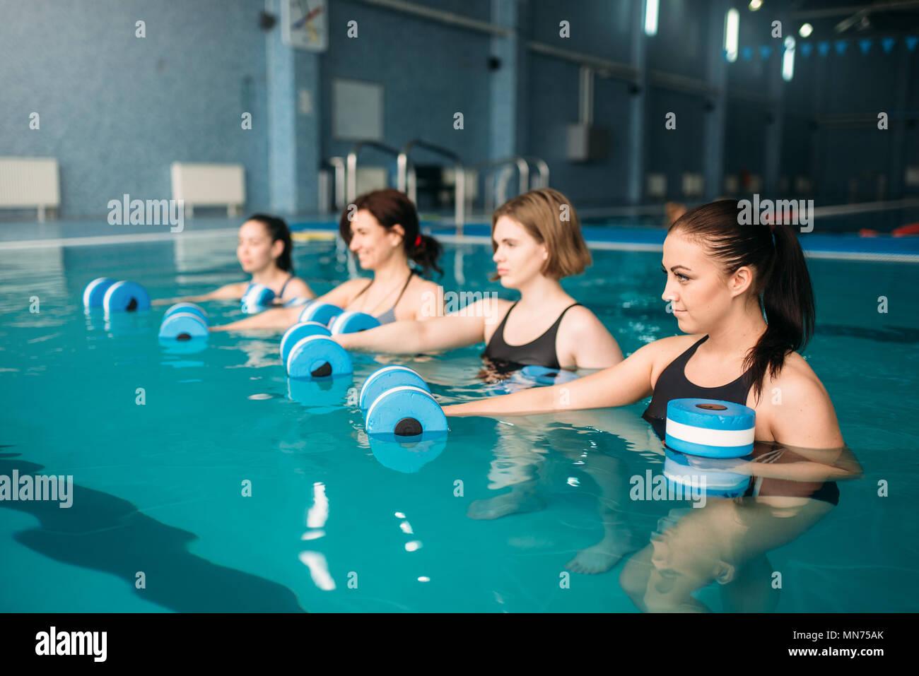 female group doing exercise with dumbbells on aqua aerobics workout