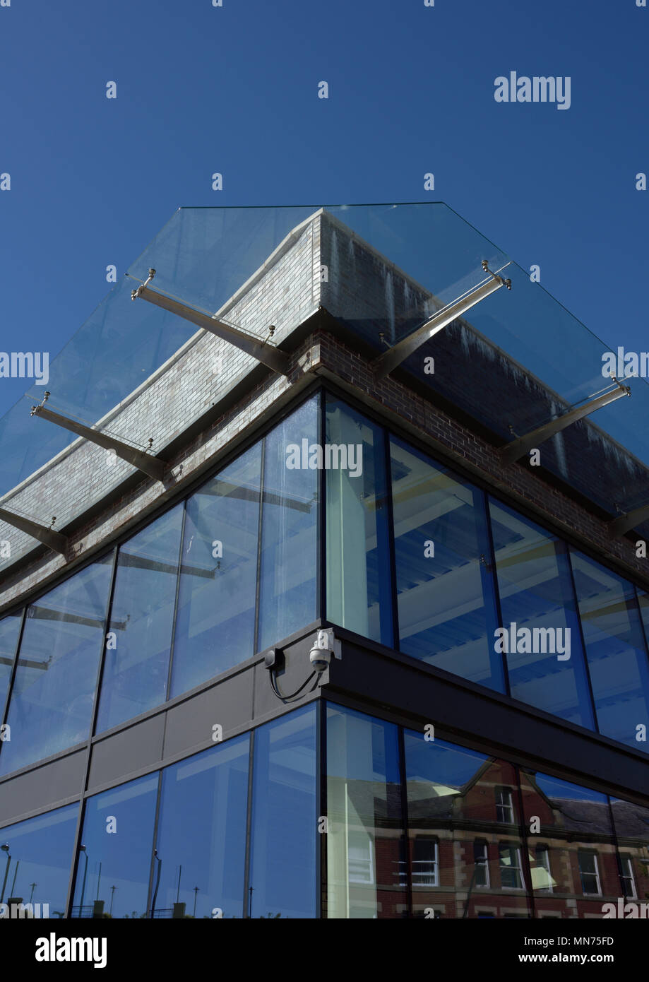 Glass canopy suspended on stainless steel brackets above glass curtain wall on new development at the rock bury lancashire uk Stock Photo