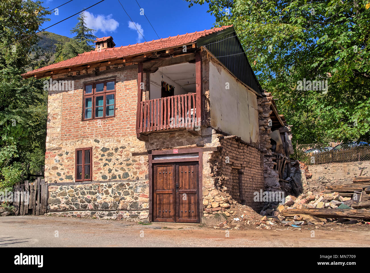Old Damaged Traditional Stone House Building with Balcony in Republic of Vevčani, FYROM Macedonia, Balkans - Stock Image