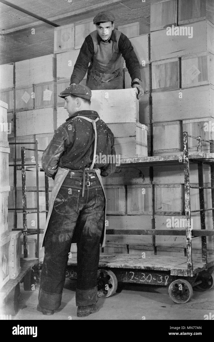 Two Workers Storing Crates of Eggs in Cold Storage Warehouse, Jersey City, New Jersey, USA, Arthur Rothstein for Farm Security Administration, January 1939 - Stock Image