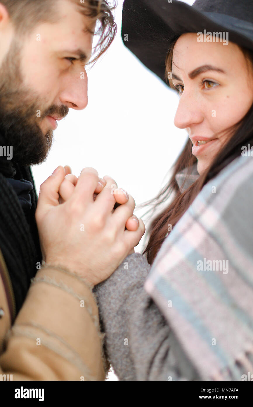 Portrait of couple wearing scarf and hat in white background. - Stock Image